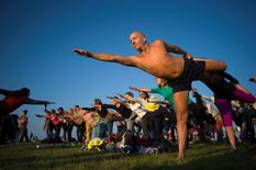 Revellers perform yoga as they celebrate the summer solstice on Salisbury Plain, in southern England June 21, 2014. REUTERS/Kieran Doherty
