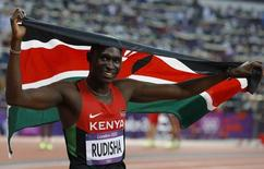 Kenya's David Lekuta Rudisha holds his national flag as he celebrates after winning the men's 800m final with a new world record at the London 2012 Olympic Games at the Olympic Stadium August 9, 2012. REUTERS/Phil Noble