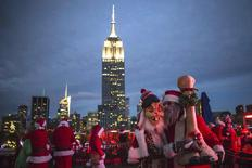 The Empire State Building is seen in the background as revelers taking part in SantaCon are pictured at a top a rooftop bar after sunset in Midtown Manhattan, New York  December 13, 2014. REUTERS/Elizabeth Shafiroff