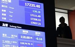 Un hombre junto a una pantalla electrónica que muestra el índice Nikkei en la bolsa de Tokio, 15 diciembre, 2014. Las bolsas de Asia estaban bajo presión el lunes luego de que los precios del petróleo se hundieron brevemente a nuevos mínimos en cinco años y medio en una sesión volátil. REUTERS/Yuya Shino