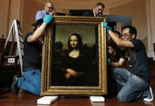 "Movers prepare to hang Leonardo da Vinci's ""Early Mona Lisa"" painting ahead of its exhibition at The Arts House in Singapore in this file picture taken December 12, 2014. REUTERS/Edgar Su/Files"
