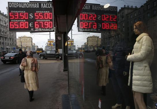 People walk along a street past a board showing currency exchange rates in Moscow, December 3, 2014. REUTERS/Maxim Zmeyev