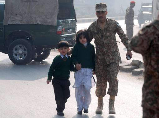 A soldier escorts schoolchildren after they were rescued from from the Army Public School that is under attack by Taliban gunmen in Peshawar, December 16, 2014. REUTERS/Khuram Parvez