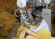 Trabajadores confeccionan trajes protectores en una fábrica de Lakeland Industries en Weifang. Imagen de archivo, 28 octubre, 2014. La actividad del sector manufacturero de China se contrajo en diciembre por primera vez en siete meses debido a una baja en los nuevos pedidos industriales, mostró el martes una encuesta preliminar entre empresarios, lo que refuerza la posibilidad de que la economía requiera un mayor estímulo. REUTERS/China Daily