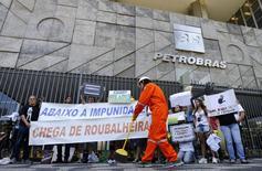 Manifestante varre a entrada da sede da Petrobras durante protesto contra corrupção. 16/12/2014 REUTERS/Sergio Moraes
