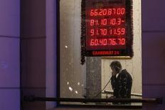 Мужчина говорит по телефону в здании на фоне вывески пункта обмена валюты в Москве 16 декабря 2014 года. Рубль торгуется в минусе на полуденной сессии среды после разнонаправленных движений начала дня - по оценке дилеров, сократилось предложение валюты от корпораций, а разъяснения Минфина о продажах валютных остатков не произвели впечатления на участников валютного рынка, хотя первой реакцией рубля было движение на сессионные пики. REUTERS/Maxim Zmeyev