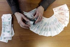 Un empleado de una compañía local cuenta rublos rusos en Stavropol, 17 diciembre, 2014.  La dramática caída del rublo se ralentizaba el miércoles, cuando el Gobierno vendía divisa extranjera para apoyar su moneda tras un descenso del 50 por ciento frente al dólar en lo que va del año. REUTERS/Eduard Korniyenko