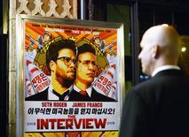 """Segurança na entrada de um cinema em frente ao pôster do filme """"A Entrevista"""", em Los Angeles. 11/12/2014 REUTERS/Kevork Djansezian"""