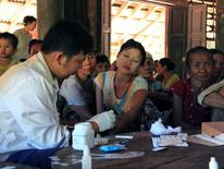 A government health worker takes a blood sample from a woman to be tested for malaria in Ta Gay Laung village hall in Hpa-An district in Kayin state, south-eastern Myanmar, November 28, 2014. REUTERS/Astrid Zweynert