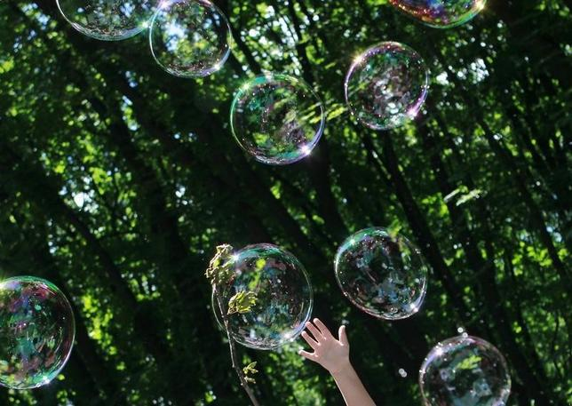 A child plays with soap bubbles at an event to support autistic children and their families in a park in Kiev May 28, 2013.  REUTERS/Gleb Garanich