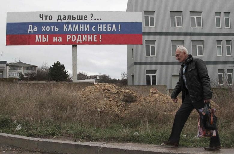 A man carries a bag attached with an orange and black ribbon of St. George as he walks past a billboard in the Crimean port of Sevastopol, November 29, 2014. The billboard reads: ''What's next? At least the stones are from the sky! We are at home!'' REUTERS/Pavel Rebrov