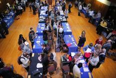 Postulantes a empleos en una feria laboral en Cambridge, EEUU, oct 16 2014. El número de estadounidenses que solicitó el seguro de desempleo por primera vez bajó imprevistamente la semana pasada, sugiriendo que el mercado laboral continuó fortaleciéndose.  REUTERS/Brian Snyder