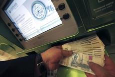 Человек снимает деньги из банкомата в Сбербанка в Санкт-Петербурге 5 ноября 2014 года. Российский Минфин предложил удвоить страховку по депозитам до 1,4 миллиона рублей в попытке укрепить доверие к банковской системе после обвала рубля. REUTERS/Alexander Demianchuk