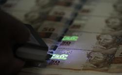 Funcionário verifica folhas de papel-moeda durante visita à Casa da Moeda. 23/08/2012 REUTERS/Sergio Moraes