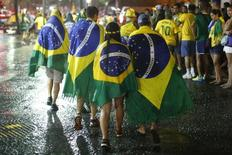 Brazil soccer fans walk in the rain after watching a broadcast of their team's loss against Germany in their 2014 World Cup semi-final match, in Rio de Janeiro July 8, 2014.  REUTERS/Jorge Silva