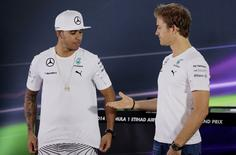 Mercedes Formula One driver Nico Rosberg (R) of Germany offers a hand to Mercedes Formula One driver Lewis Hamilton of Britain before a news conference at the Yas Marina circuit before the start of the Abu Dhabi Grand Prix, in this November 20, 2014 file photo. REUTERS/Caren Firouz/Files