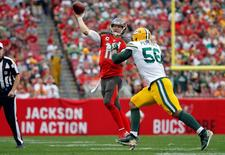 Dec 21, 2014; Tampa, FL, USA; Tampa Bay Buccaneers quarterback Josh McCown (12) throws the ball as Green Bay Packers outside linebacker Julius Peppers (56) pressures during the first half at Raymond James Stadium. Mandatory Credit: Kim Klement-USA TODAY Sports