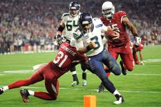 Dec 21, 2014; Glendale, AZ, USA; Seattle Seahawks quarterback Russell Wilson (3) rushes for a touchdown during the second half against the Arizona Cardinals at University of Phoenix Stadium. Joe Camporeale-USA TODAY Sports