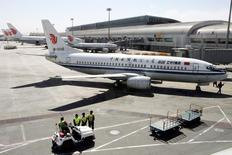 Chinese workers stand in front of an Air China Boeing B737 aircraft at Beijing Airport March 23, 2005. REUTERS/Claro Cortes IV