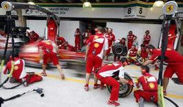 Ferrari Formula One mechanics practise a pit stop with the car of driver Fernando Alonso of Spain at Interlagos race track in Sao Paulo November 6, 2014.  REUTERS/Paulo Whitaker