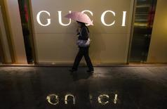 A woman holding an umbrella walks past a company logo of a Gucci boutique outside a shopping mall amid rainfall in central Guangzhou, Guangdong province February 25, 2014. REUTERS/Alex Lee