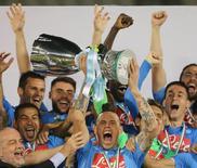 """Игроки """"Наполи"""" радуются победе в матче за Суперкубок Испании в Дохе 22 декабря 2014 года. """"Наполи"""" не дал сбыться надеждам """"Ювентуса"""" на рекордную седьмую победу в матче за Суперкубок Италии, обыграв туринцев в драматичной серии из 18 послематчевых пенальти. REUTERS/Fadi Al-Assaad"""