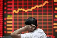 Розничный инвестор в брокерской конторе в Китае в городе Хуайбэй в китайской провинции Аньхой 9 сентября 2013 года. Частные компании Китая, судя по всему, обеспечат еще год активных слияний и поглощений в Азии после того, как объем сделок достиг рекорда в текущем году, при этом розничный, финансовый и технологический сектора станут наиболее активными в этой области. REUTERS/Stringer
