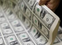 Однодолларовые купюры в процессе производства в Бюро по выпуску денежных знаков и ценных бумаг в Вашингтоне 14 ноября 2014 года. Курс доллара к корзине шести основных валют близок к максимуму 8,5 лет, так как рынок ожидает более раннего повышения процентных ставок ФРС после сообщения о неожиданно быстром росте американской экономики. REUTERS/Gary Cameron