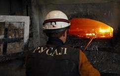 Рабочий в цеху Красноярского алюминиевого завода Русала 8 июля 2014 года. Крупнейший в мире производитель алюминия Русал планирует за счет дивидендов от Норильского никеля досрочно погасить $300 миллионов долга перед кредиторами, включая госбанки Сбербанк и Газпромбанк. REUTERS/Ilya Naymushin