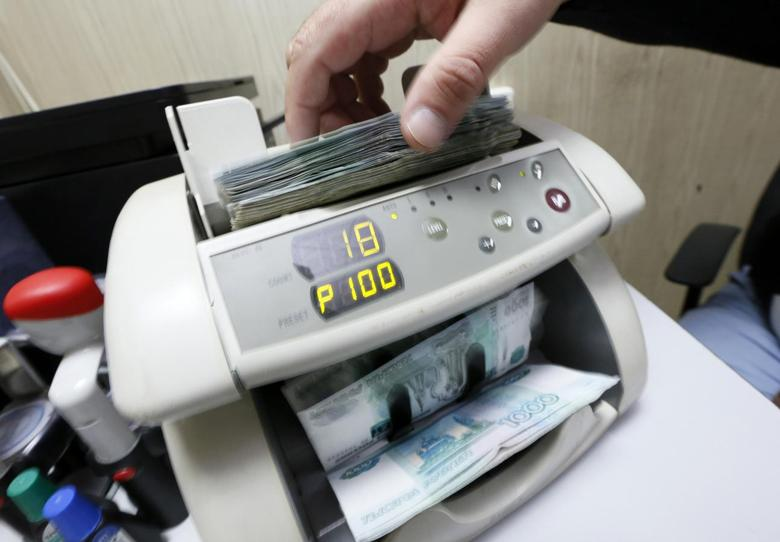 An employee uses a machine while counting Russian ruble banknotes at a private company's office in Krasnoyarsk, Siberia, December 17, 2014. REUTERS/Ilya Naymushin