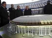 Russia's Sports Minister Vitaly Mutko (L), President Vladimir Putin (C) and FIFA President Sepp Blatter (2nd R) listens to Moscow's Mayor Sergei Sobyanin at the Luzhniki Stadium, which is under construction, in Moscow, October 28, 2014. REUTERS/Mikhail Klimentyev/RIA Novosti/Kremlin