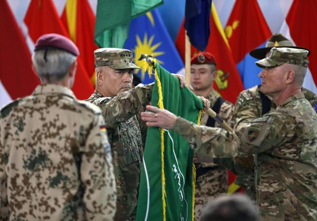 U.S. General John Campbell (C), commander of NATO-led International Security Assistance Force (ISAF), folds the flag of the ISAF during the change of mission ceremony in Kabul, December 28, 2014. The American-led coalition in Afghanistan officially ended its combat mission on Sunday after a more than 13 year war that ousted the Taliban government in 2001. REUTERS/Omar Sobhani