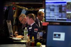 Трейдеры на фондовой бирже в Нью-Йорке 29 декабря 2014 года. Американские фондовые индексы завершили вялые торги понедельника почти без изменений, но индекс S&P 500 достиг очередного максимума. REUTERS/Carlo Allegri