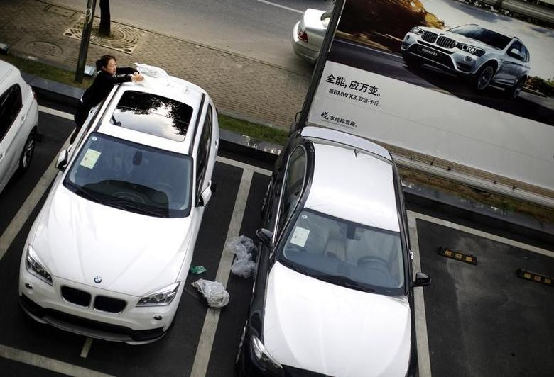 An employee removes a plastic cover from a new BMW car at a BMW dealership from the Baoxin Auto Group in Shanghai September 2, 2014. REUTERS/Carlos Barria
