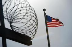 Флаг США над забором тюрьмы в Гуантанамо 10 декабря 2008 года. Три йеменца и два тунисца, удерживаемые более десяти лет в Гуантанамо, переведены в Казахстан, сообщил во вторник Пентагон, продолжая подготовку к закрытию военной тюрьмы на арендуемой у Кубы военной базе. REUTERS/Mandel Ngan/Pool