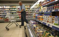 Покупатель в продуктовом магазине в Москве 7 августа 2014 года. Инфляция в России в 2014 году, по предварительным данным, составила 11,4 процента, в декабре - 2,6 процента, сообщил Росстат в последний день года. REUTERS/Maxim Zmeyev