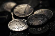 Monedas de yuan chino vistas en una fotografía tomada en Shanghái. Imagen de archivo, 7 abril, 2013.  El yuan cerró el miércoles a 6,2040 unidades contra el dólar, con lo que anota en 2014 su primera pérdida anual significativa desde 2005, cuando se realizó una histórica revaluación de la moneda china. REUTERS/Carlos Barria