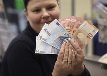 Caissière d'un magasin de Vilnius. La Lituanie a officiellement intégré jeudi la zone euro, un changement de monnaie qui vise entre autres à ancrer un peu plus le pays dans le camp européen au moment où la Russie fait étalage de sa force militaire dans la région. /Photo prise le 1er janvier 2015/REUTERS/Ints Kalnins