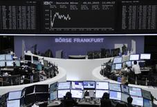 Traders are pictured at their desks in front of the German share price index DAX board at the Frankfurt stock exchange on January 5, 2015. REUTERS/Remote/Stringer