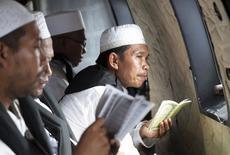 Clérigo muçulmano durante oração por vítimas do voo QZ 8501 da AirAsia, dentro de helicóptero da Força Aérea da Indonésia sobre o Mar de Java. 06/01/2015 REUTERS/Achmad Ibrahim/Pool