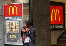 A woman stands in front of a McDonald's store in Tokyo December 16, 2014.  REUTERS/Issei Kato