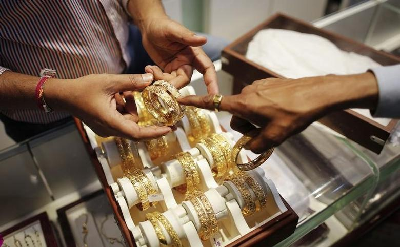 An employee shows gold bangles to a customer at a jewellery showroom on the occasion of Dhanteras, a Hindu festival associated with Lakshmi, the goddess of wealth, at a market in Mumbai in this file photo taken November 1, 2013.  REUTERS/Danish Siddiqui/Files