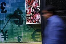 Una persona camina frente a una casa de cambios en el centro de Santiago, oct 30 2014. Las monedas de mercado emergente van a seguir bajo presión durante 2015, según un sondeo de Reuters, pero no se debilitarían tanto como el año pasado, ya que los precios de las materias primas y políticas monetarias menos flexibles en Estados Unidos ya habrían sido asimiladas en los precios.  REUTERS/Ivan Alvarado