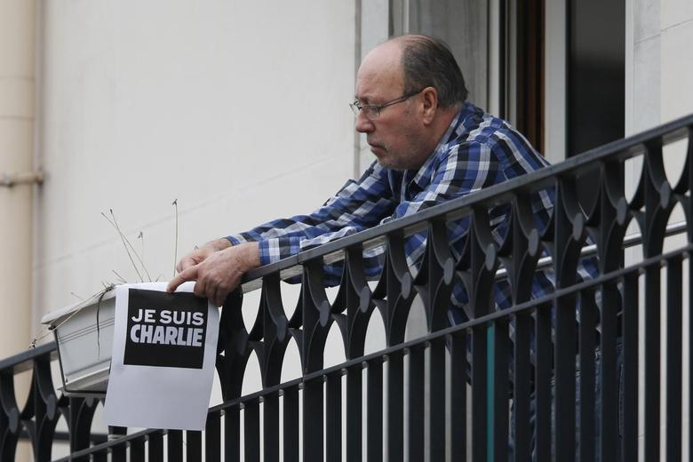 A resident holds a placard which reads ''I am Charlie'' on a balcony near the scene after a shooting at the Paris offices of Charlie Hebdo January 7, 2015. REUTERS/Charles Platiau