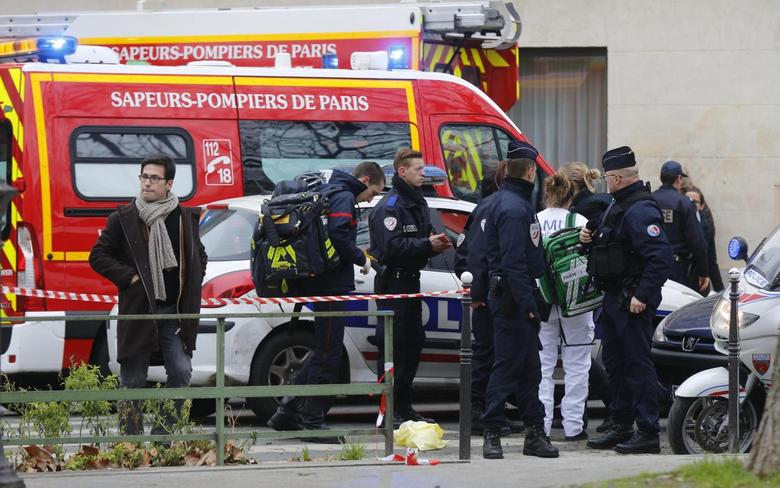 A view shows policemen and rescue members at the scene after a shooting at the Paris offices of Charlie Hebdo, January 7, 2015. REUTERS/Jacky Naegelen