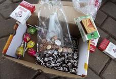 A bag of new Zimbabwean coins, candies and packs of cigarettes are seen in Harare, December 18, 2014. REUTERS/Philimon Bulawayo