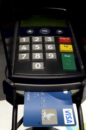 A credit card is seen inserted in a card reader at a store in Stockholm in this November 2013 file photo.  REUTERS/Hass Holmberg