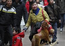 A woman holds onto her child with one hand and toys with the other at a railway station in Beijing January 14, 2014. REUTERS/China Daily