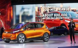 General Motors CEO Mary Barra speaks next to the Chevrolet Bolt EV electric concept car (L) and the 2016 Chevrolet Volt hybrid (rear) after they were unveiled during the first press preview day of the North American International Auto Show in Detroit, Michigan January 12, 2014.  REUTERS/Rebecca Cook