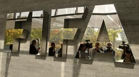 Journalists are reflected in a logo at the FIFA headquarters after a meeting of the executive committee in Zurich October 4, 2013.REUTERS/Arnd Wiegmann